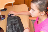 Young hispanic girl working on a computer — Stock Photo