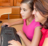 Hispanic girl and her mother working on a computer — Stock Photo