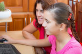 Hispanic girl and her young mother working on a computer — Stock Photo
