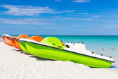 Colorful pedalos docked at a tropical beach — Stock Photo