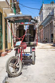 Street in Havana with an old three wheeled bicycle — Stock Photo