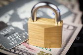 Closed padlock over a stack of money and cards — Stock Photo