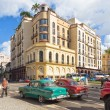 Old american cars near a modern hotel in Havana — Stockfoto