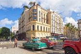 Old american cars near a modern hotel in Havana — Stock Photo