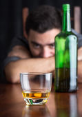 Glass of whisky with an out of focus drunk and depressed man — Stock Photo