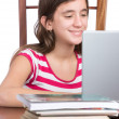 Teenager doing homework or browsing the web on her laptop — Stock Photo
