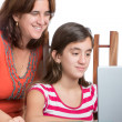 Teenager and her mom working on a laptop computer — Stock Photo #38620615