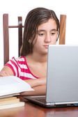 Teenager using her laptop isolated on white — Stock Photo