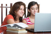Hispanic teen and her mother working or browsing the web on a la — Stock Photo
