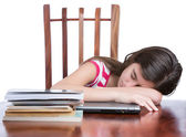 Tired girl sleeping over her laptop with a stack of books on the table — Stock Photo