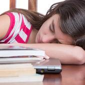 Garota cansada, dormindo sobre seu laptop com uma pilha de livros sobre a mesa — Foto Stock