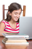 Teenager doing homework on her laptop isolated on white — Stock Photo