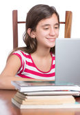 Teenager doing homework or browsing the web on her laptop — Stok fotoğraf