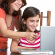Stock Photo: Hispanic teen and her mother browsing web and laughing
