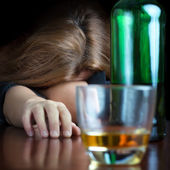 Drunk alcoholic woman sleeping on a table — Stock Photo