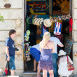 Постер, плакат: Tourists buying souvenirs in Havana