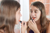 Hispanic teen putting on lipstick in front of a mirror — Stock Photo