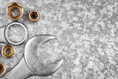 Wrench tools and nuts on a metallic background — 图库照片
