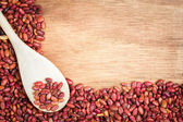 Red beans and a spoon framing a wooden background — Stock Photo