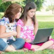 Hispanic girl and her mother browsing the web outdoors — Stock Photo #43958975