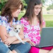Hispanic girl and her mother browsing the web outdoors — Stock Photo #43959001