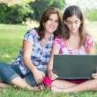 Hispanic girl and her young mother using a laptop computer outdo — Stock Photo