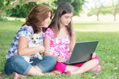 Hispanic girl and her mother browsing the web outdoors — Stock Photo