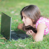 Teenage girl laying in the grass and using her laptop — Stock Photo