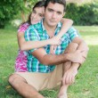 Hispanic teenage girl hugging her father at a park outdoors — Stock Photo #44149253