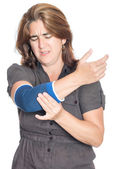 Woman with injured elbow using an elastic support — Stock Photo
