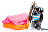 Electric iron and colorful clothes isolated on white — Stock Photo
