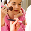 Portrait of a beautiful young woman looking at the mirror, applying make up on her face — Stock Photo