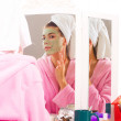 Beautiful young woman in towel doing cosmetic mask on her face — Stock Photo