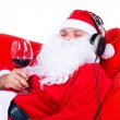 Christmas Santa Claus chilling out with a glass of red wine, isolated on white. — Stock Photo