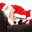 Stock Photo: Christmas SantClaus chilling out isolated on white.
