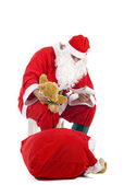 Christmas Santa Claus checking his lists, isolated on white. — Stock Photo