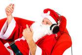 Santa hört musik über kopfhörer — Stockfoto