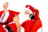 Santa listens to music on headphones — Stock Photo