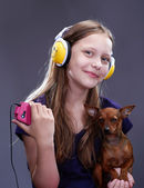 Studio shot of a smiling teen girl with headphones and doggy — Stock Photo