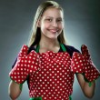 Portrait of a little housewife showing thumbs up — Stock Photo