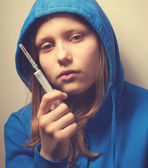 Dark portrait of a junk teen girl with syringe — Stockfoto