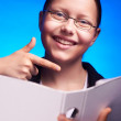 Young businesswoman in eyeglasses shows on folder with finger — Stock Photo #51345579