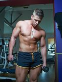 Guy doing exercises with dumbbells — Foto Stock