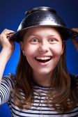 Girl with a colander on her head — Stock Photo