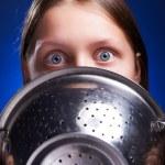 Teen girl hiding her face behind colander — Stock Photo #51666619