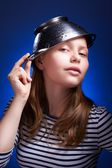 Calm teen girl with a colander on her head — Stock Photo