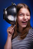 Teen girl holding colander and grimacing — Stock Photo