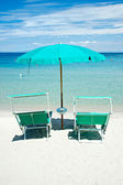 Two beach chairs with green umbrella. — Stock Photo