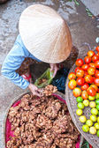 Vietnamese woman selling ginger in a market, Ho chi minh city, V — Stock Photo