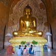 A monk and three women praying inside htilominlo Temple, Bagan, - Foto Stock